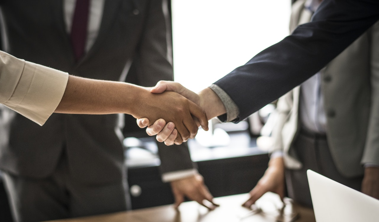 client and outsourcing services agency shaking hands over a deal